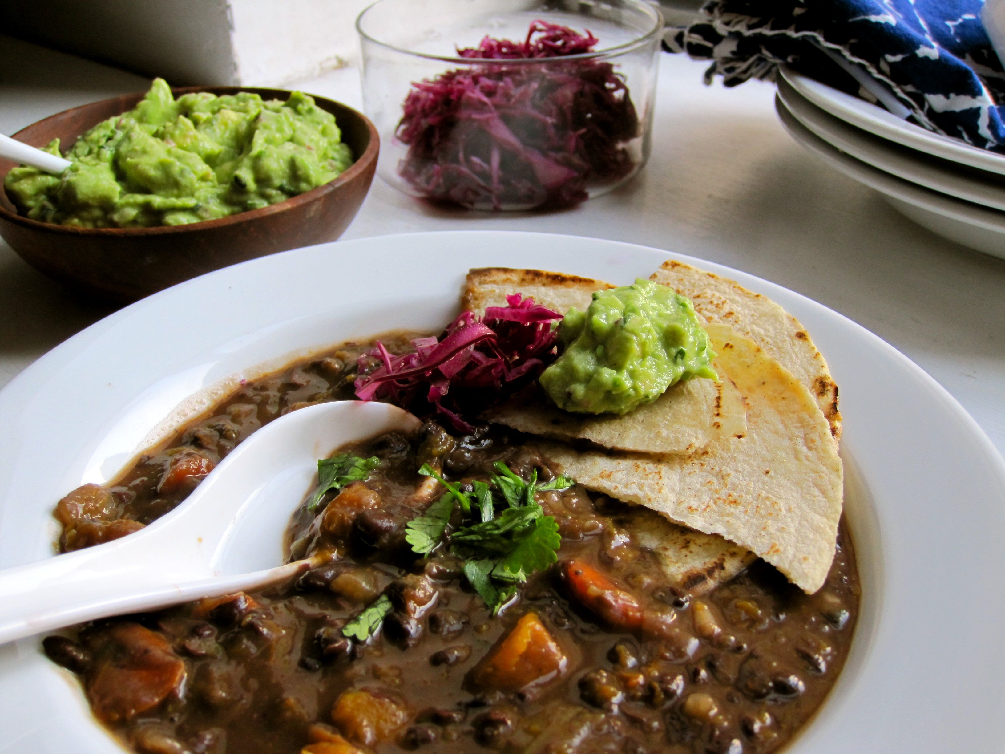 soup with tortilla, guacamole and pickled red cabbage